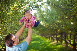 Dad plays with daughter in the orchard