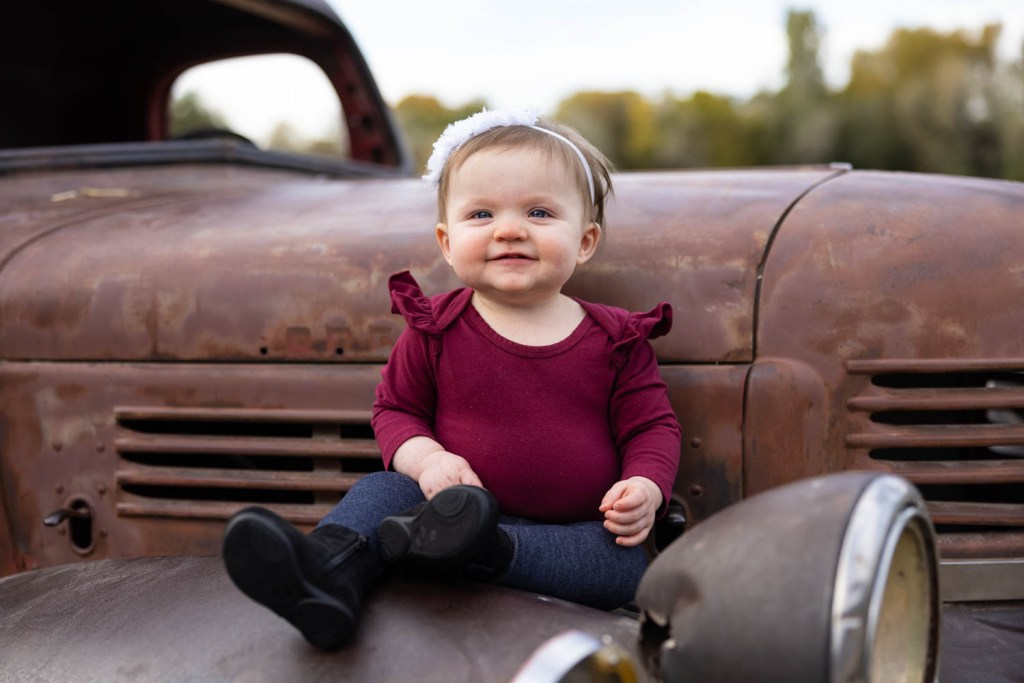 Baby girl smiles for the camera while sitting on an antique truck