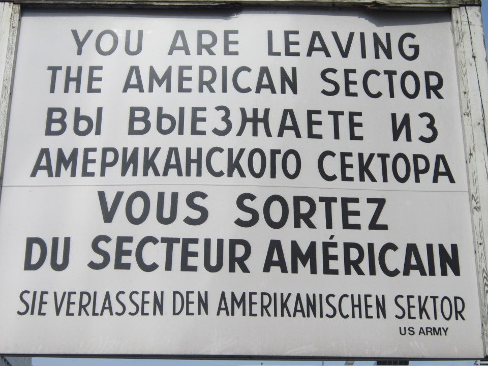 things to do in berlin - sign at checkpoint charlie 'you are leaving the american sector' in english, russian and german
