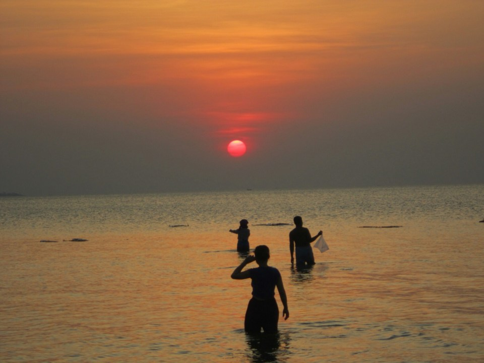 Locals go out into the sea to catch crabs at sunset in Kep, Cambodia