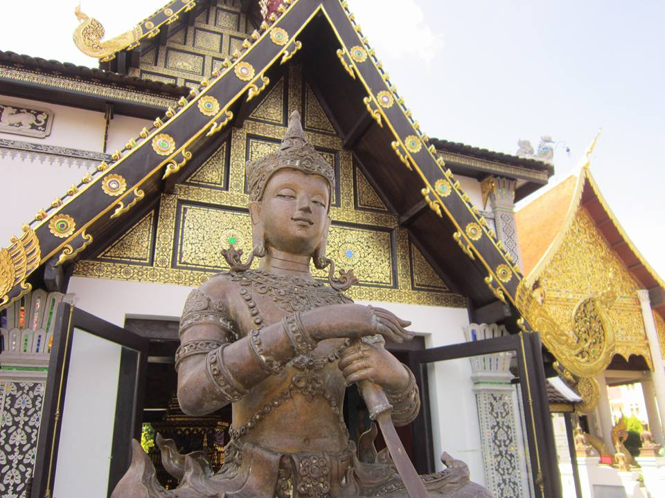 A bronze Buddhist statue in Chiang Mai in front of a temple entrance.