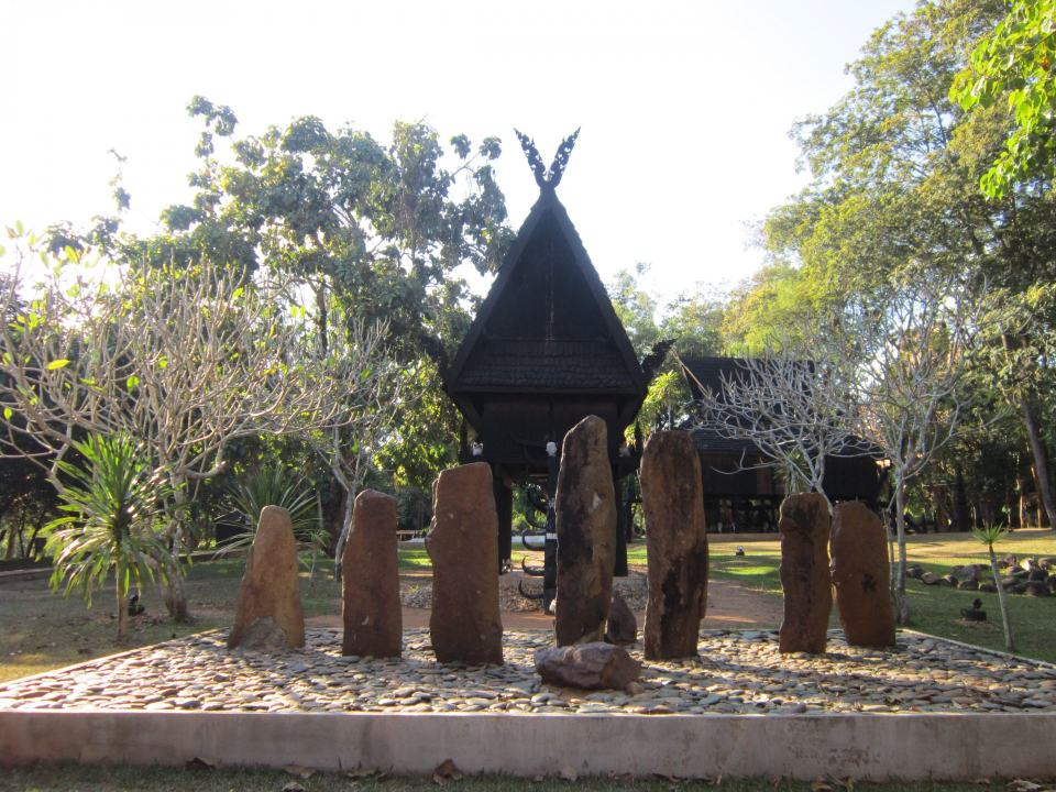 A set of stones set out in decorative fashion, in front of black wooden buildings at The Baandam Museum .