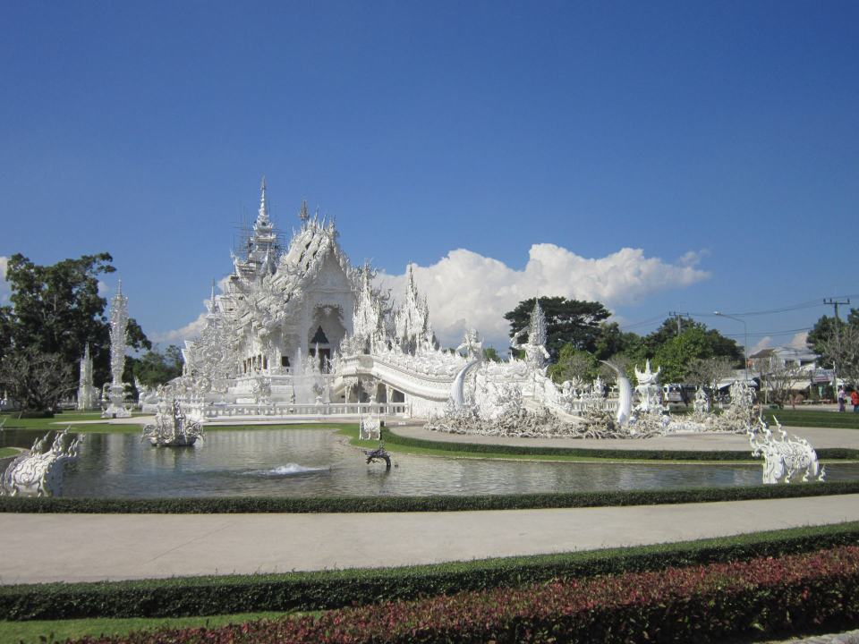 A view of the White temple in Chaing Rai, across a large pond filled with water.