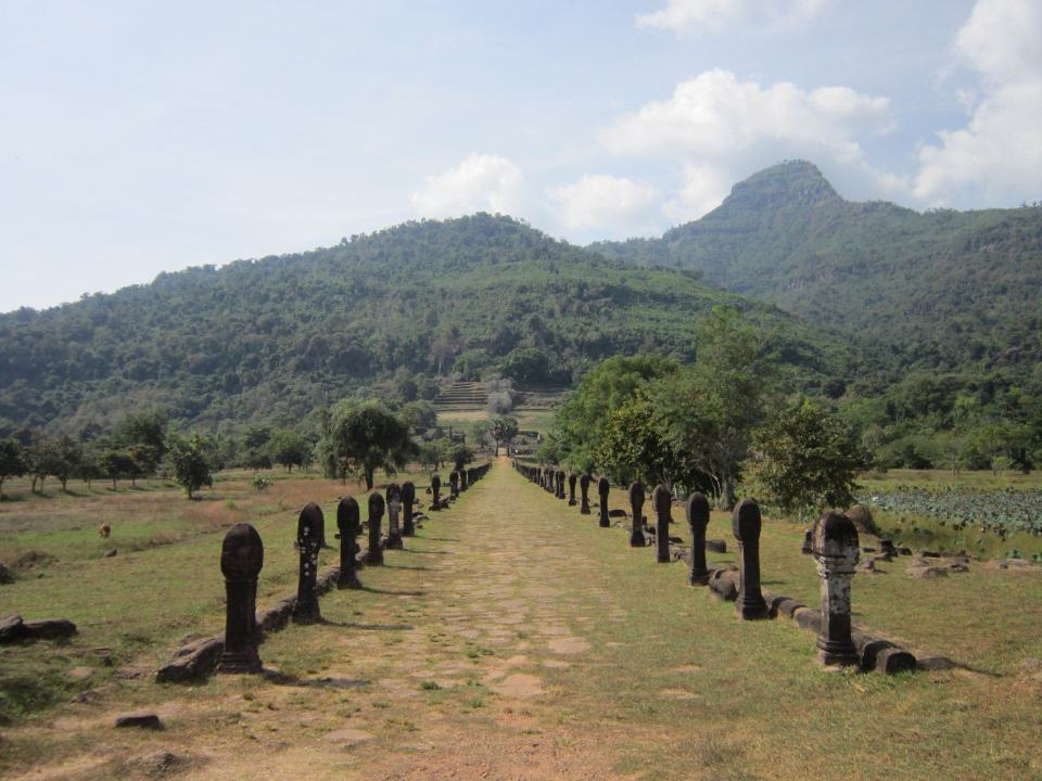 The approach to Vat Phou in Laos. Through a path with pillars on each side, with the temple on a hill in the background.