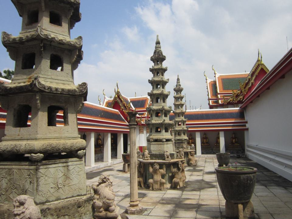 Buddhist pillars standing in a courtyard, surrounded by building with brightly covered roofs. At Wat Pho, a Southeast Asian temple.