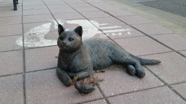 Happy cat with its catch, just relaxing on the street corner.