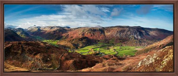 View over the lush green fields of the Borrowdale valley to the Honister Pass in Cumbria