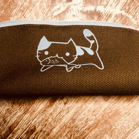 Items: stationery, pencil case (brown with cat eating fish / zipper)