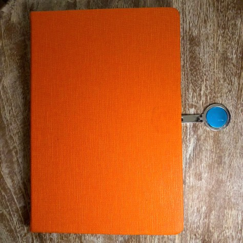 Items: stationery, notebook (orange with clasp)