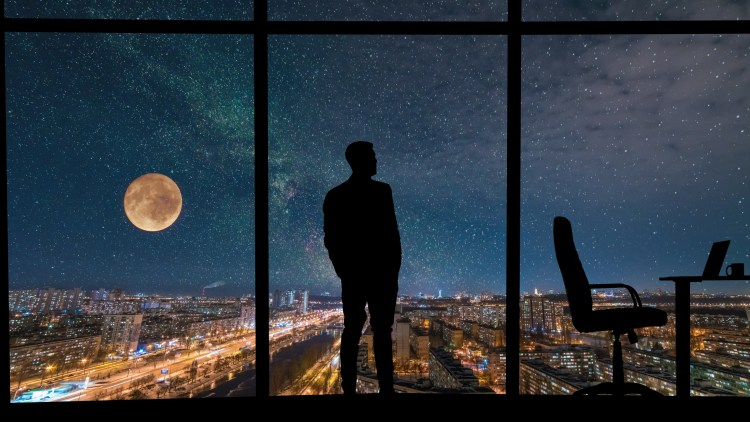 The man standing near the panoramic window on city with starry sky background