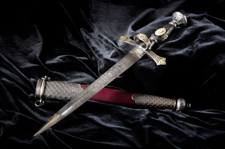 A dagger with a red-tinted hilt and a dark background having an ominous look