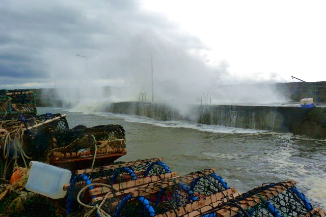 wave crashes over the harbour wall