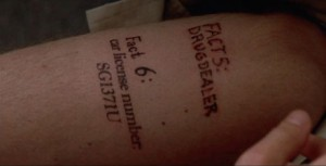 "Figure 1: Throughout the movie, the protagonist repeatedly ""discovers"" that his body is covered in tattoos like this, and thus repeatedly is reminded of what he's learned so far in his pursuit of his wife's murderer."