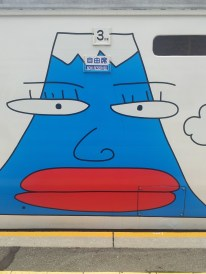 A painting of Mt Fuji on the side of a train