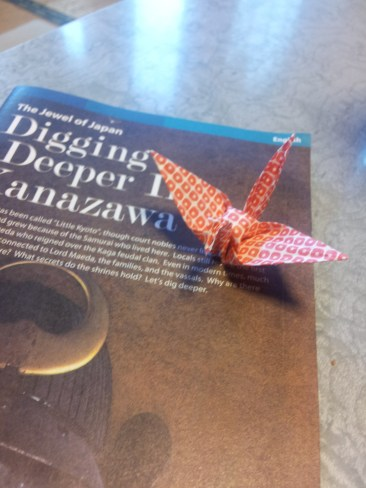 An origami crane sitting on a guide book