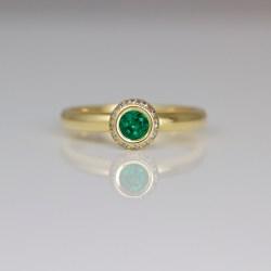 modern emerald ring with diamond halo