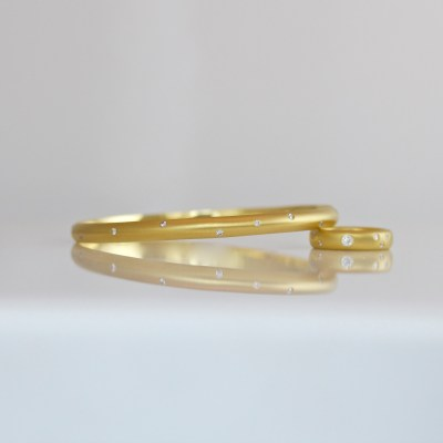 Contemporary 18ct gold bangle with flush set diamonds