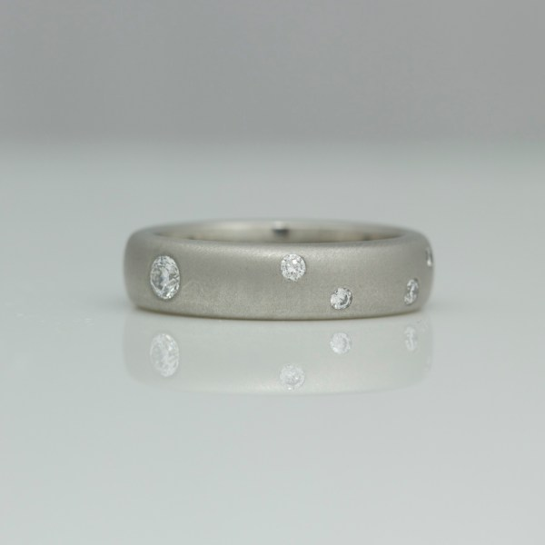 Platinum ring, various sizes of diamonds randomly flush set.