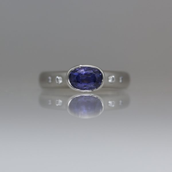 Purple oval sapphire set in Platinum diamond set ring
