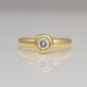 18ct yellow gold ring with a rub-over set diamond solitaire