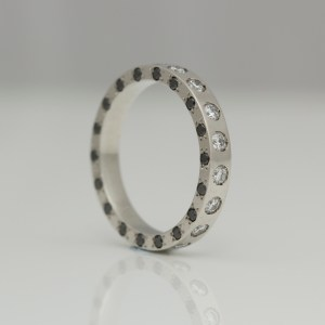 Platinum ring set with black & white diamonds on three edges