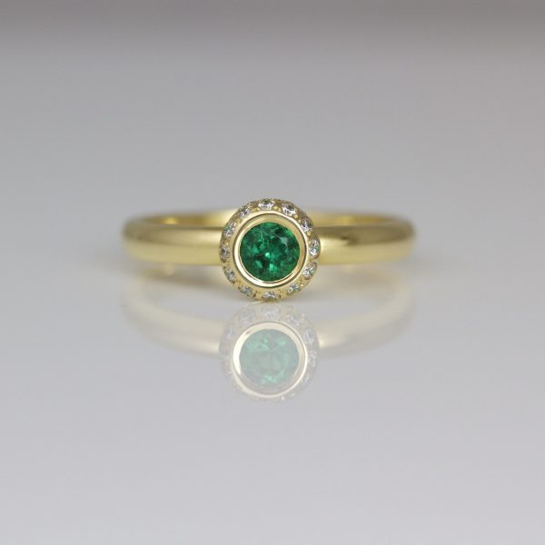 Emerald framed with diamonds 18ct yellow gold ring
