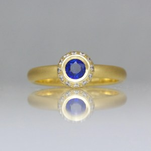 Sapphire framed with diamonds 18ct gold ring