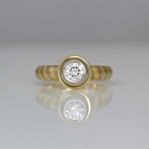 Diagonal stripe ring with solitaire diamond rub-over set