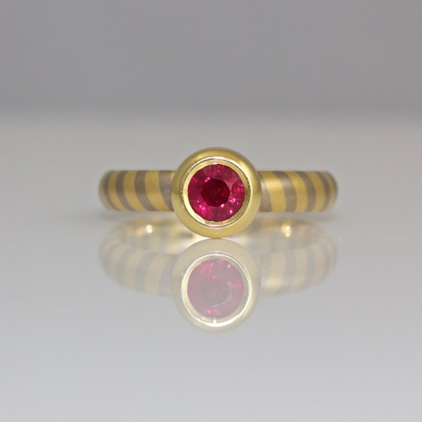 Ruby rub-over set in yellow gold on diagonal stripe band