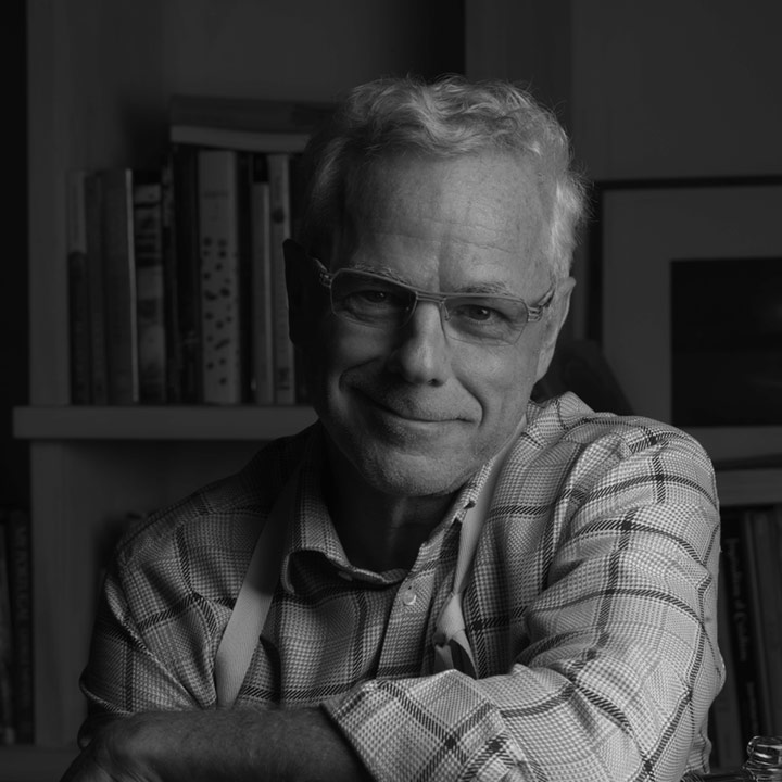 Chef David Bouley wearing smart glasses and a checked shirt, photographed in front of a bookshelf