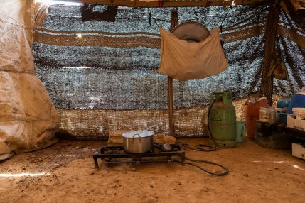 The kitchen area in a make-shift tent in an informal encampment in Neaime. With a dirt floor and made of whatever material was available the tent doesn't provide any protection against the weather, the cold or heat.