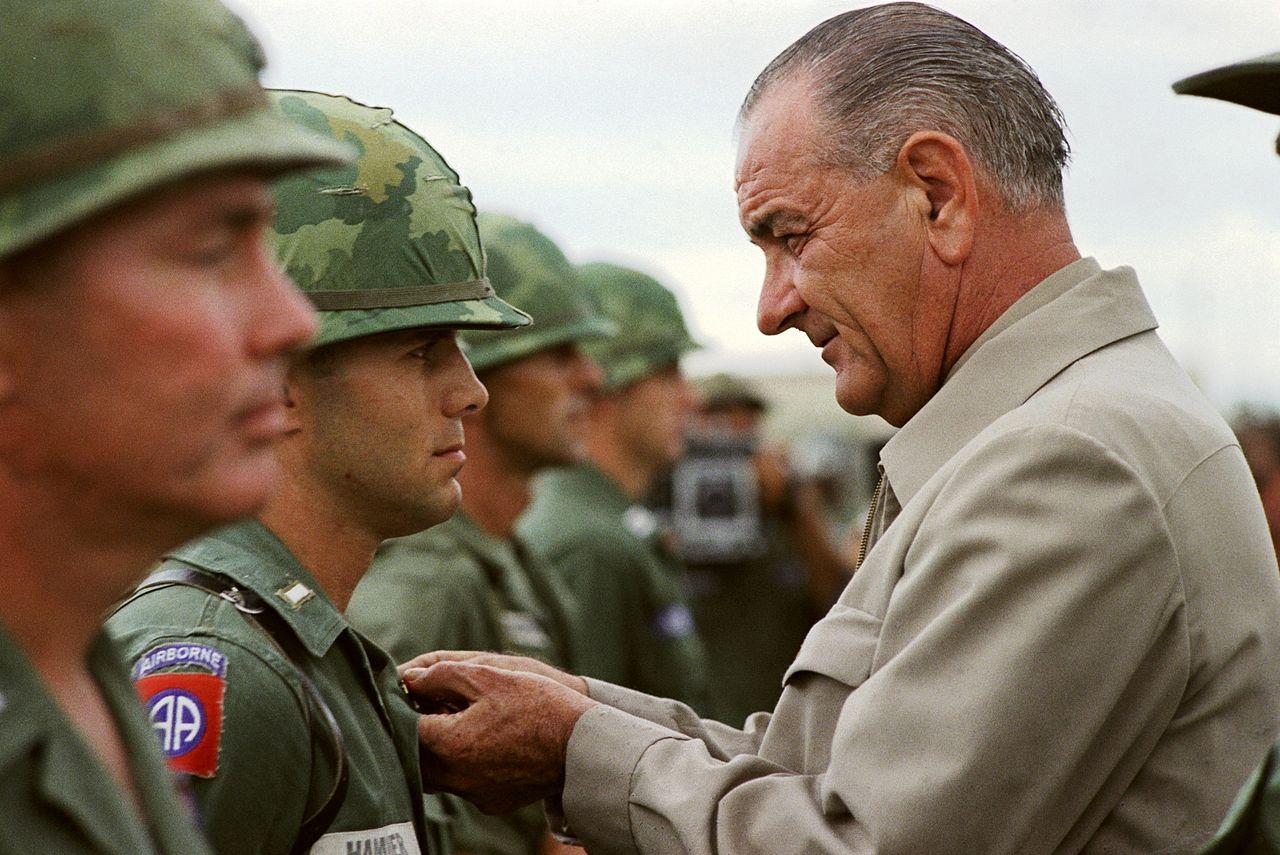 LBJ pinning an award onto a Soldier
