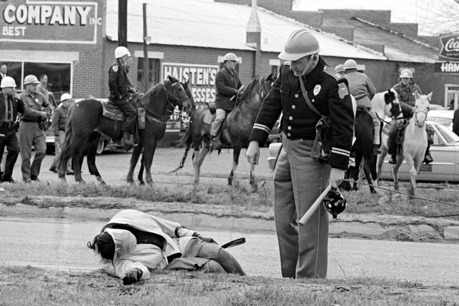 Police Officer aggressively standing over a fallen protester in Selma
