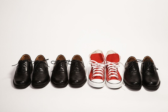 Four pair of shoes. 3 black dress shoes and a pair of red sneakers