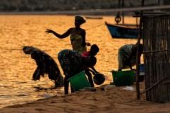 La luce dorata dei primi raggi del sole del mattino crea magnifiche silhouettes delle donne impegnate a lavare panni e tegami nelle acque del lago. Il silenzio è rotto solamente da qualche canzone e dalle risate dei bambini che giocano in acqua.