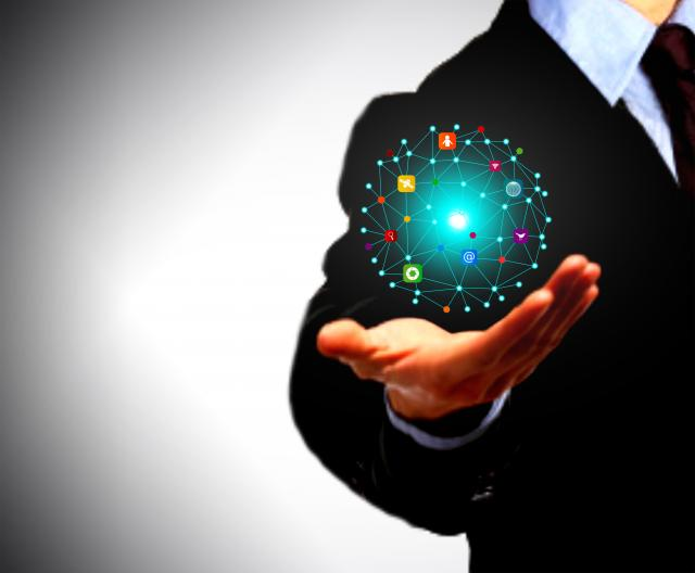 Businessman holding a globe with information technology icons in