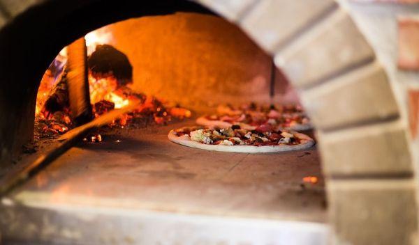 Horno de leña con pizzas dentro