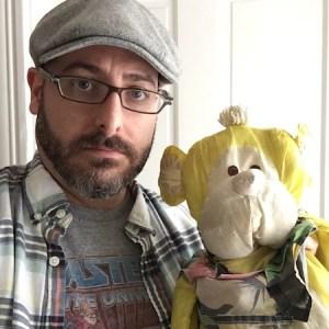Photo of Josh Funk holding a stuffed monkey toy