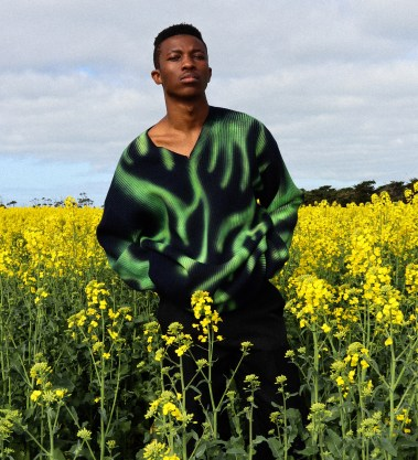 DJ and creative Shayne Tino stands in a field of yellow flowers wearing a Balenciaga V-Neck sweater featuring a black and fluorescent green tie dye pattern.