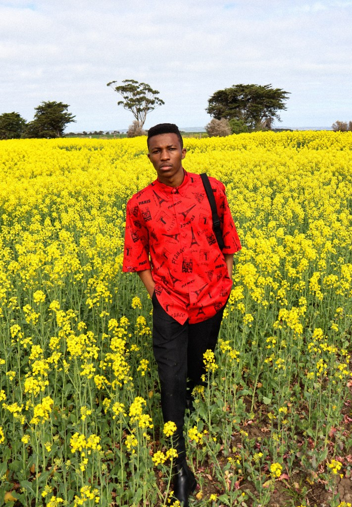 DJ and creative Shayne Tino stands in a field of yellow flowers wearing a bright red button up shirt. It has an Eiffel Tower print.