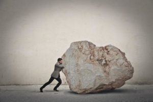 Business person pushing a big rock