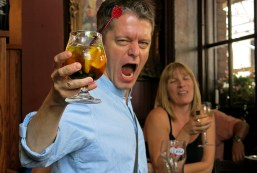photo of white male early 40s in English pub yelling into camera whilst holding a glass of Pimms
