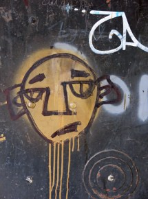 street art graffiti Mostar Bosnia yellow face on black metal