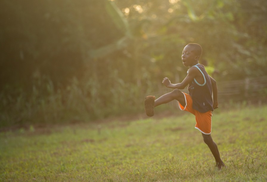 A young boy playing soccer at sunset in Ghana.
