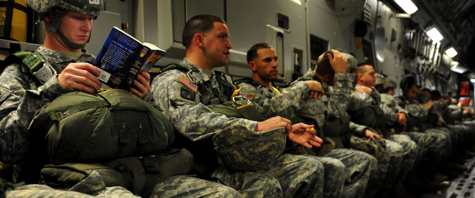 Soldiers sitting in cargo plane, waiting to jump, reading.