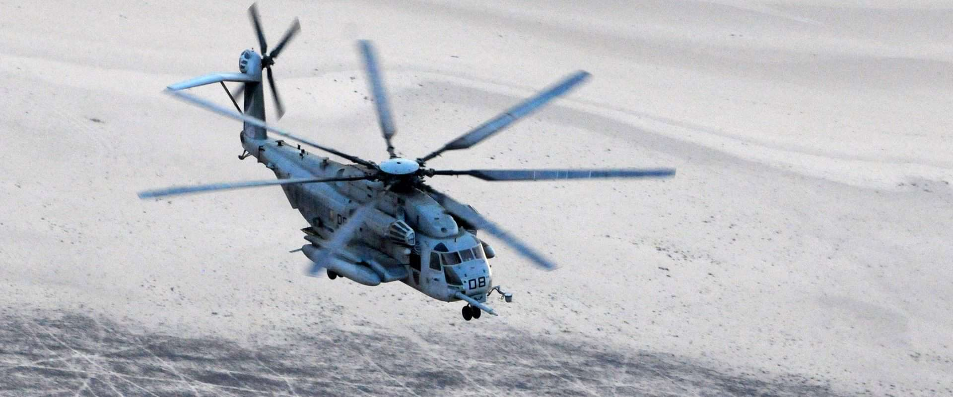 Questions and Answers, an MH-53 Pave Low helicopter flies over desert