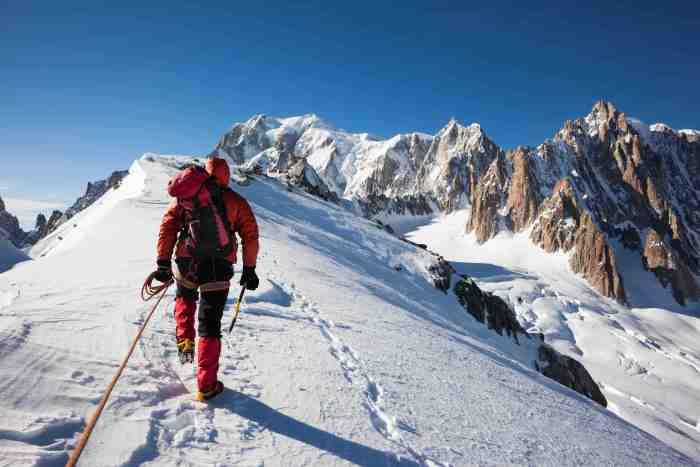 Mountaneer climbs a snowy ridge in Mont Blanc, France. Enterprise, diligence, team work: mountaneering concepts.