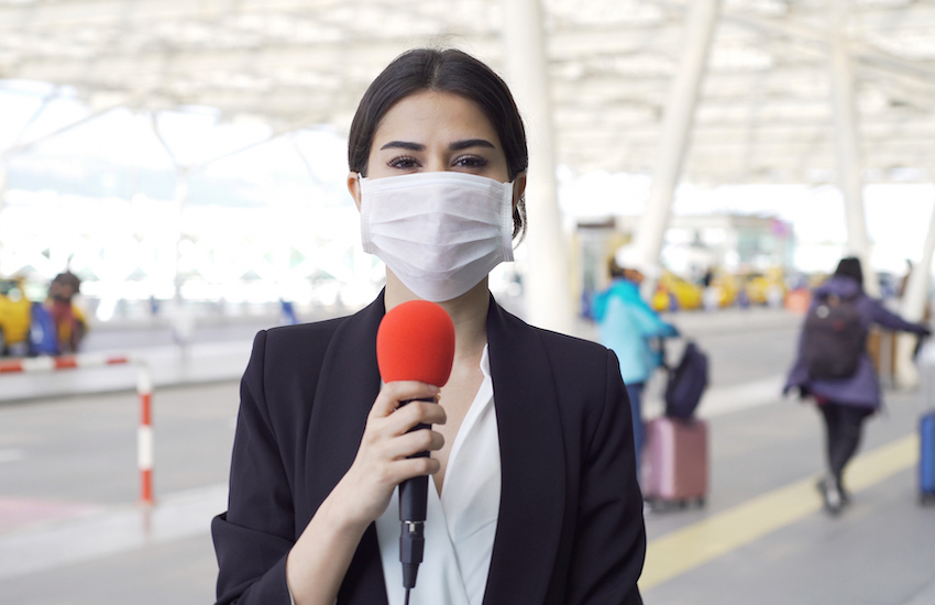 TV reporter wearing a mask.