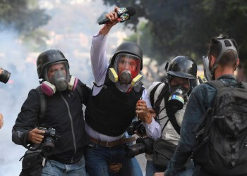 Venezuelan VPITV journalist Gregory Jaimes (C) is assisted by colleagues after being injured during clashes between anti-government protesters and security forces on the commemoration of May Day on May 1, 2019, after a day of violent clashes on the streets of the capital spurred by Venezuela's opposition leader Juan Guaido's call on the military to rise up against President Nicolas Maduro. - Guaido called for a massive May Day protest to increase the pressure on Venezuelan President Nicolas Maduro. (Photo by Federico Parra / AFP)