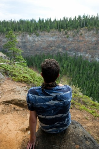 A man sits on the edge of the canyon in Wells Gray Park.